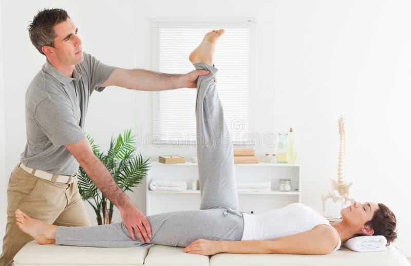 Chiropracticus het uitrekken zich het been van een wijfje stock foto's
