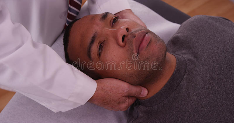 Chiropractor που ελέγχει τον τραυματισμό λαιμών του αφρικανικού αρσενικού ασθενή στοκ εικόνες με δικαίωμα ελεύθερης χρήσης