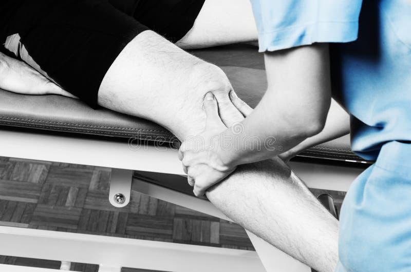 Chiropractor το /physiotherapist που κάνει ένα μασάζ γονάτων στη σκιαγραφία στοκ φωτογραφία με δικαίωμα ελεύθερης χρήσης