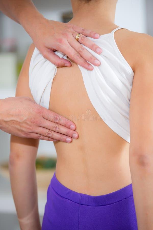Chiropractor che fa registrazione sul paziente femminile immagine stock libera da diritti
