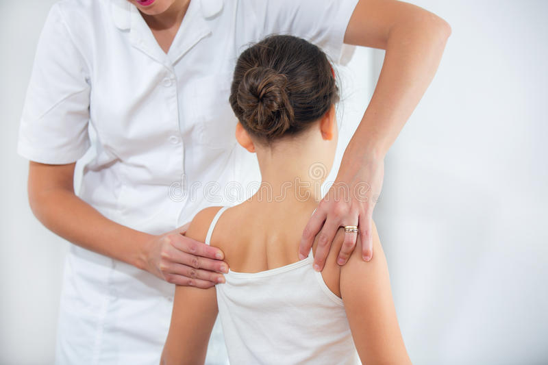 Chiropractor doing adjustment on female patient. In doctor's office stock images