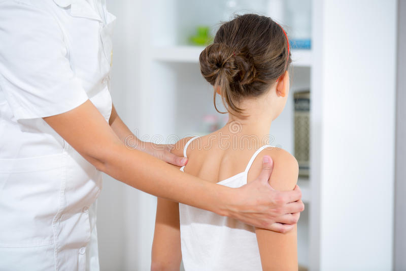 Chiropractor doing adjustment on female patient. In doctor's office royalty free stock image