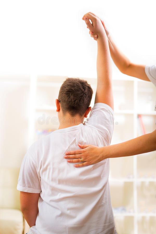 Chiropractor doing adjustment on male patient. Selective focus. Chiropractor doing adjustment on male patient royalty free stock photo
