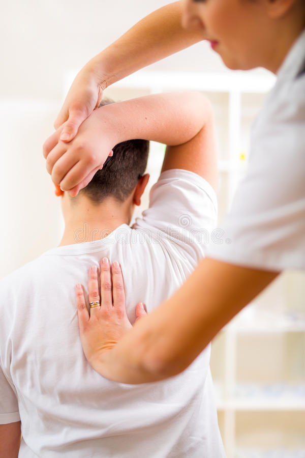 Chiropractor doing adjustment on male patient. Selective focus. Chiropractor doing adjustment on male patient stock image