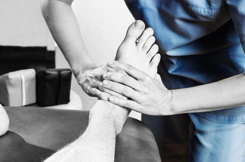 Chiropractor /physiotherapist doing a feet massage in silhouet royalty free stock photo