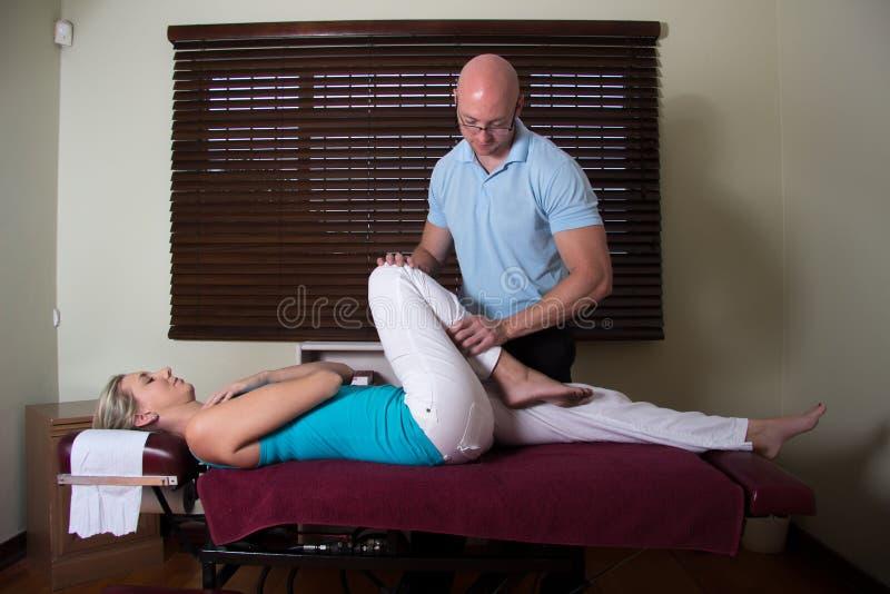 Chiroprakteur étirant la femelle la jambe patiente photographie stock libre de droits