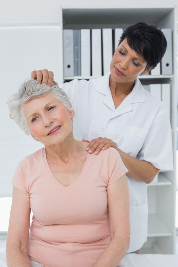Chiroprakteur féminin faisant l'ajustement de cou photo stock