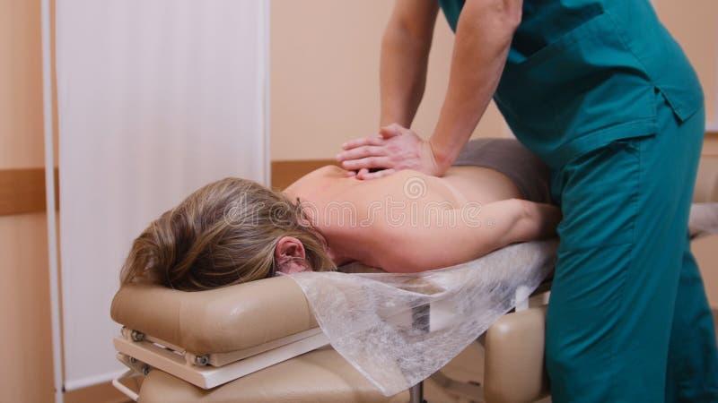 Chiroprakteur massant une femme se trouvant sur une table de massage, fléchissant l'épaule photos libres de droits