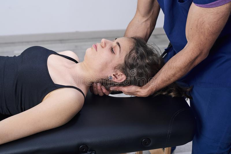 Chiropraktijk die mobiliserings cervicale stekel van een vrouw krijgen Handtherapie Neurologisch fysiek onderzoek Osteopathie, stock fotografie