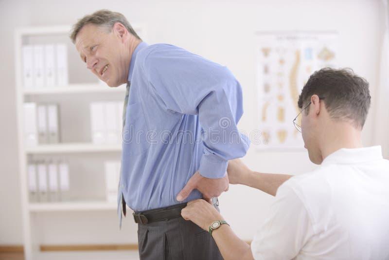Chiropraktik: Chiropraktor, der älteren Mann überprüft. stockfotos