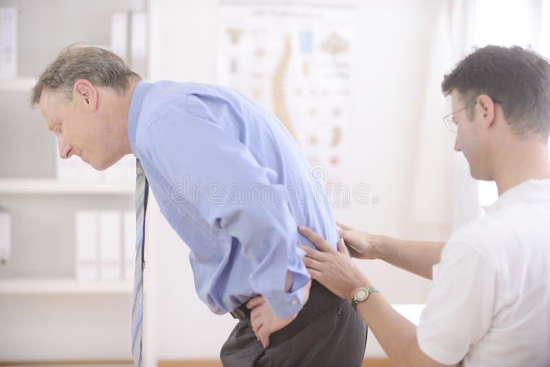 Chiropraktik: Chiropraktor, der älteren Mann überprüft. lizenzfreie stockfotos