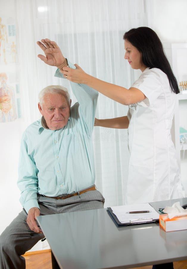 Chiropraktik: Chiropraktor, der älteren Mann im Büro überprüft stockfotografie