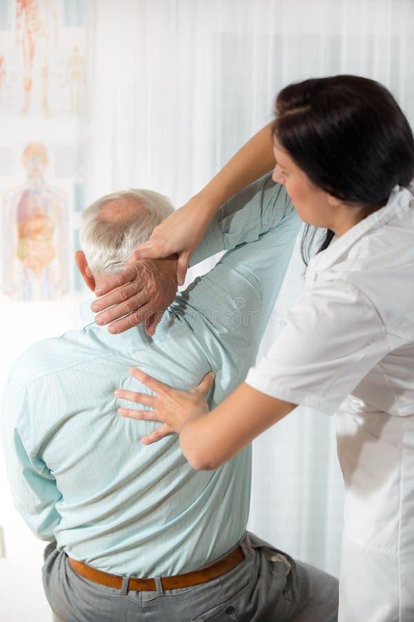Chiropraktik: Chiropraktor, der älteren Mann im Büro überprüft lizenzfreies stockfoto