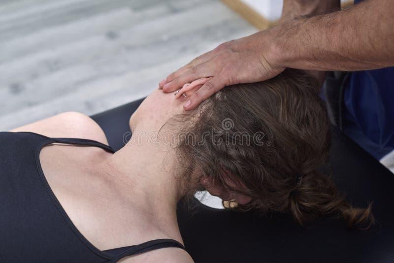 Chiropraktik, die Mobilisierung zervikalen Dorn einer Frau erhält Manuelle Therapie Neurologische körperliche Untersuchung Osteop lizenzfreies stockfoto