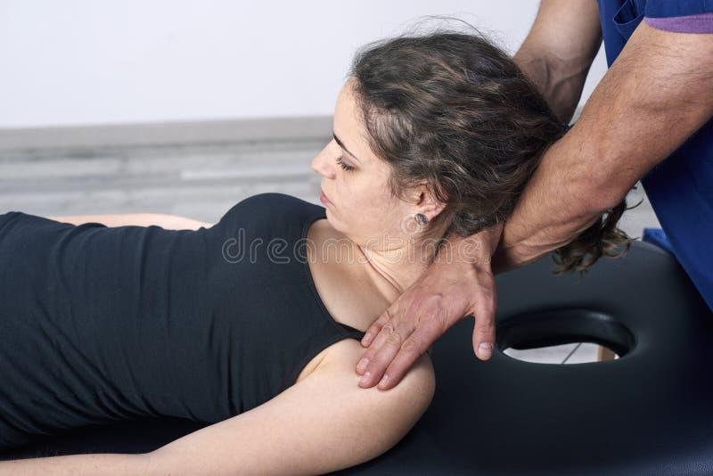 Chiropraktik, die Mobilisierung zervikalen Dorn einer Frau erhält Manuelle Therapie Neurologische körperliche Untersuchung Osteop lizenzfreies stockbild