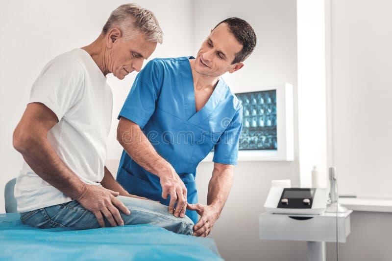 Chiropraktor in der blauen Uniform sprechend mit seinem Patienten stockfotos