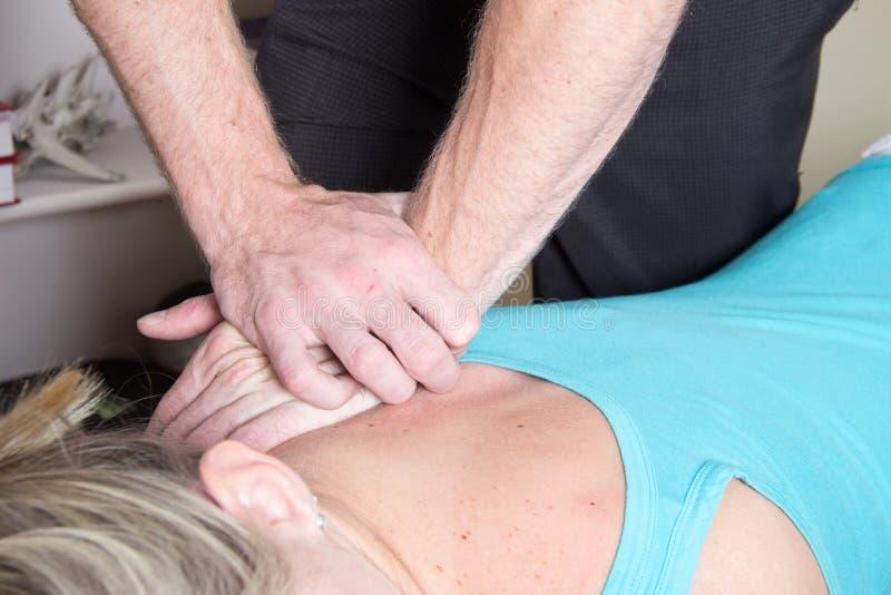 Chiropratico che tratta pressione paziente della spalla fotografia stock