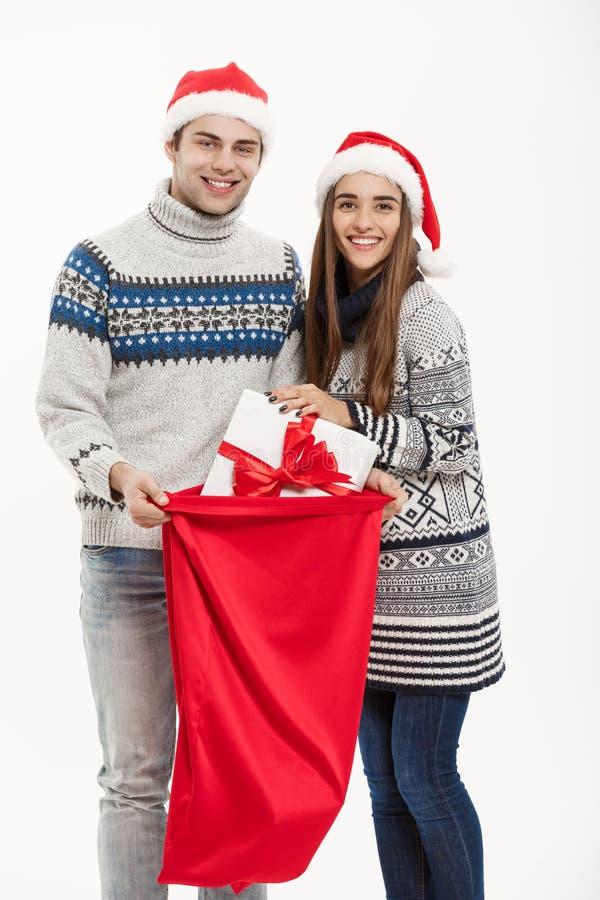 Chirstmas begrepp - ungt attraktivt par med den röda påsen för jultomten som firar den Chirstmas dagen bakgrund isolerad white fotografering för bildbyråer
