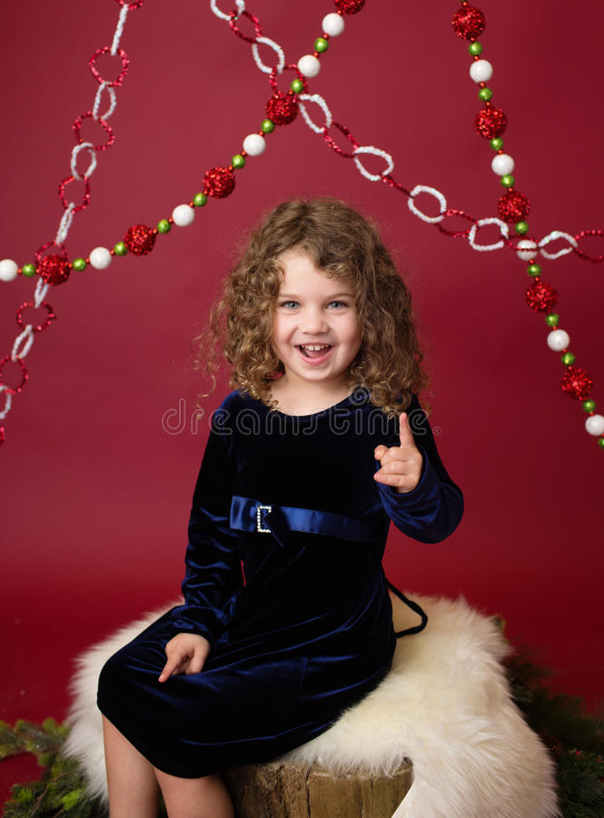 Chirstmas Child on tree stump and pine tree branches, Red Holiday royalty free stock image