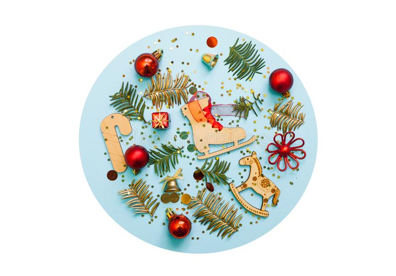 Chirstmas decorations on blue and white background. Flat lay, top view. Wood toys, red balls, pine tree branches. stock image