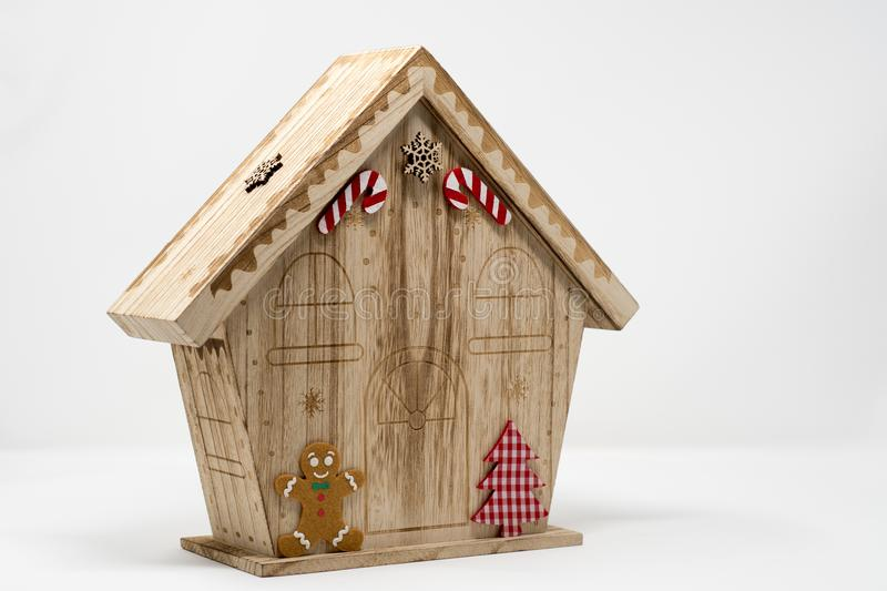 A chirstmas themed wooden model house, with candy cain, gingerbread man and checked christmas tree decoration stock image