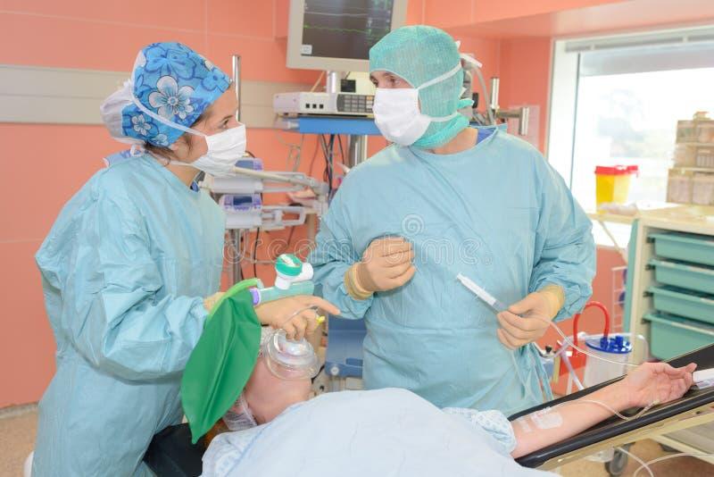 Chirurdzy dyskutuje pacjenta nagrywają funkcjonującego pokój przy szpitalem zdjęcia stock