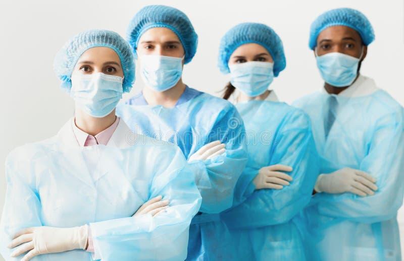 Chirurdzy Zespalają się Będący ubranym Ochronnych mundury, Stoi W rzędzie obrazy royalty free