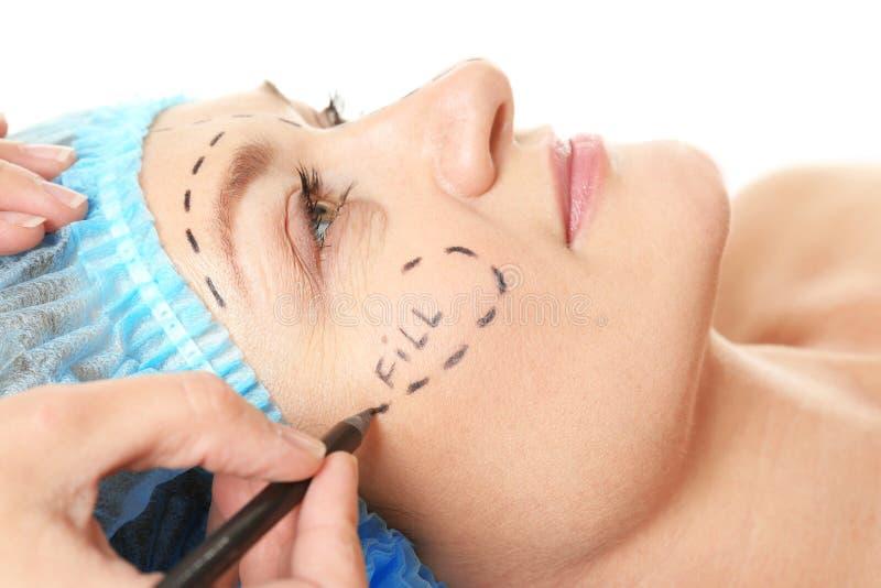 Chirurg übergibt Zeichnungskennzeichen auf weiblichem Gesicht für Operation lizenzfreies stockbild