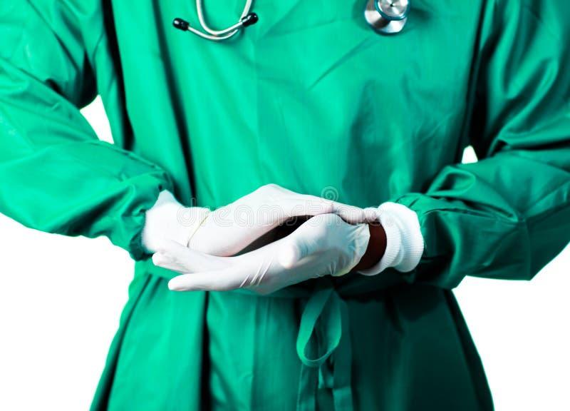 Chirurg, der auf seine Handschuhe sich setzt lizenzfreies stockbild
