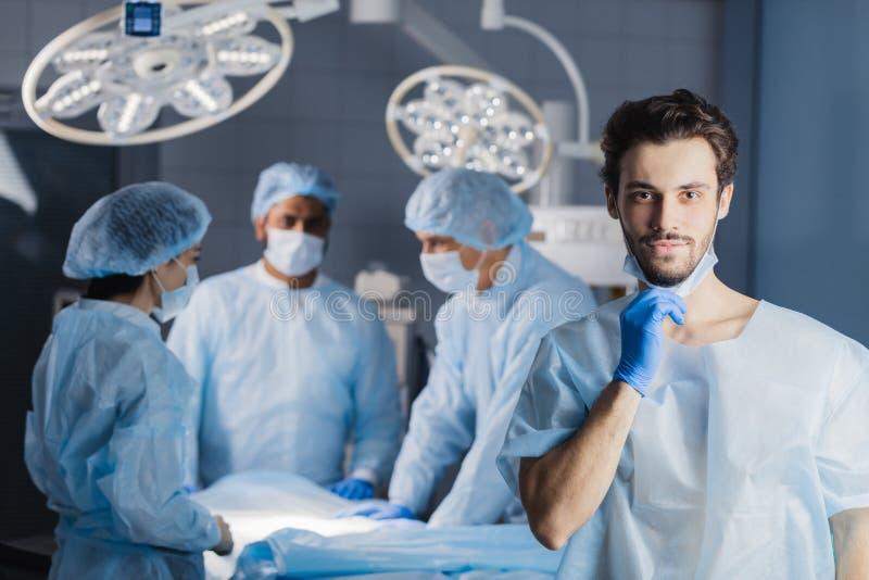 Chirurg, der Kamera mit Kollegen betrachtet lizenzfreie stockfotos