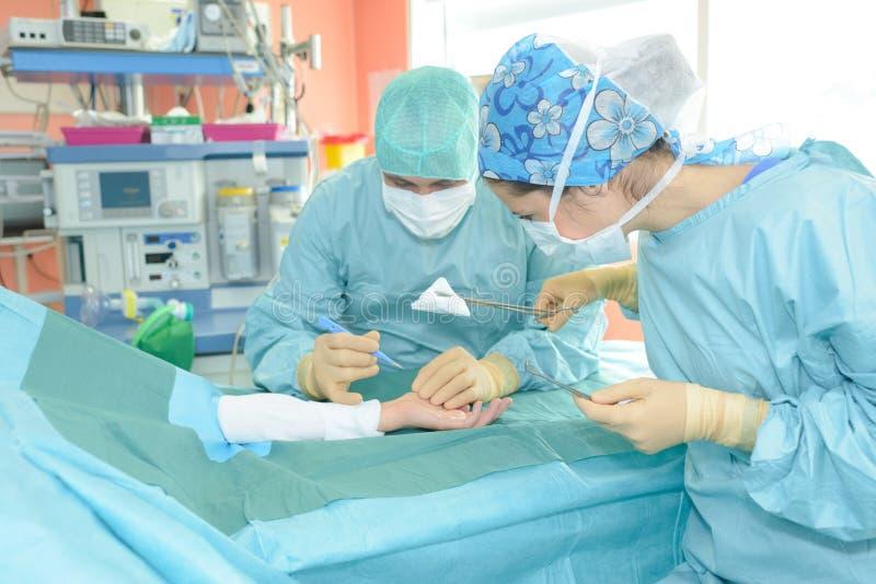 Chirurg, der Operation auf geduldiger ` s Hand durchführt lizenzfreie stockfotos
