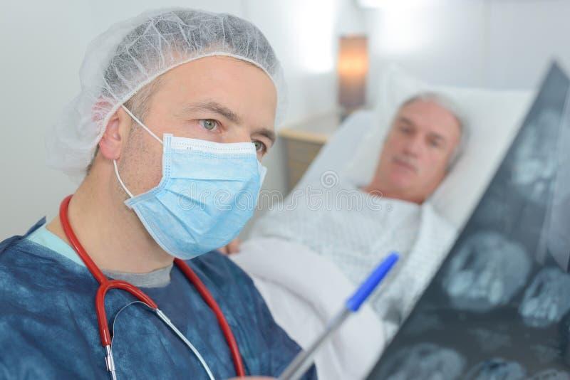 Chirurg, der Röntgenstrahlen betrachtet stockfotos