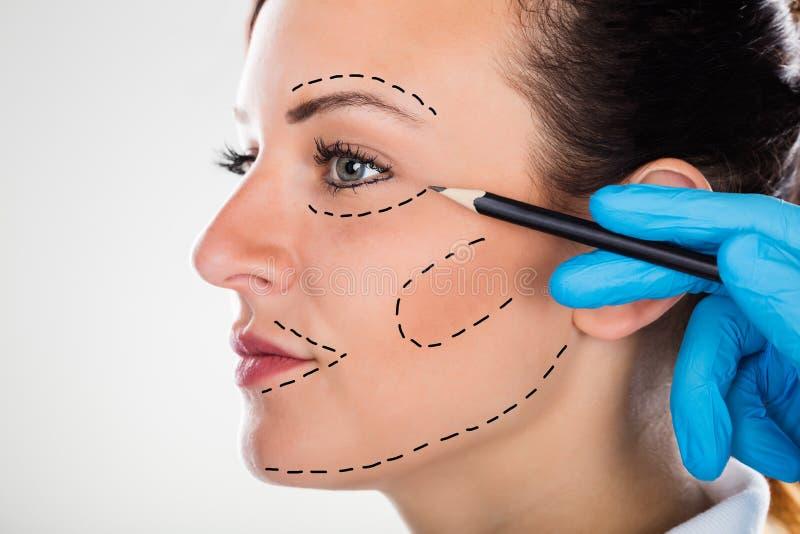 Chirurg Drawing Correction Lines op Jong Vrouwengezicht royalty-vrije stock afbeeldingen