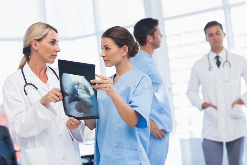 Chirurg en arts die röntgenstraal samen analyseren royalty-vrije stock fotografie