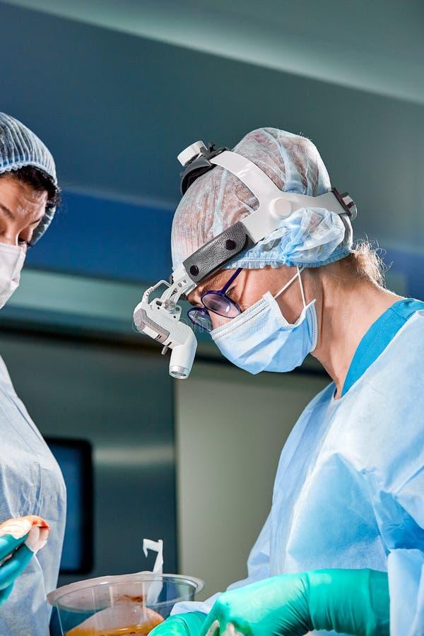 Chirurg en zijn hulp het presteren kosmetische chirurgie in het ziekenhuis werkende ruimte Chirurg in masker die loupes dragen ti royalty-vrije stock fotografie