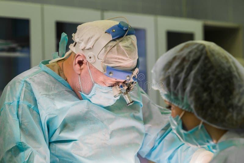 Chirurg en zijn medewerker tijdens medische procedure in het ziekenhuis o stock foto