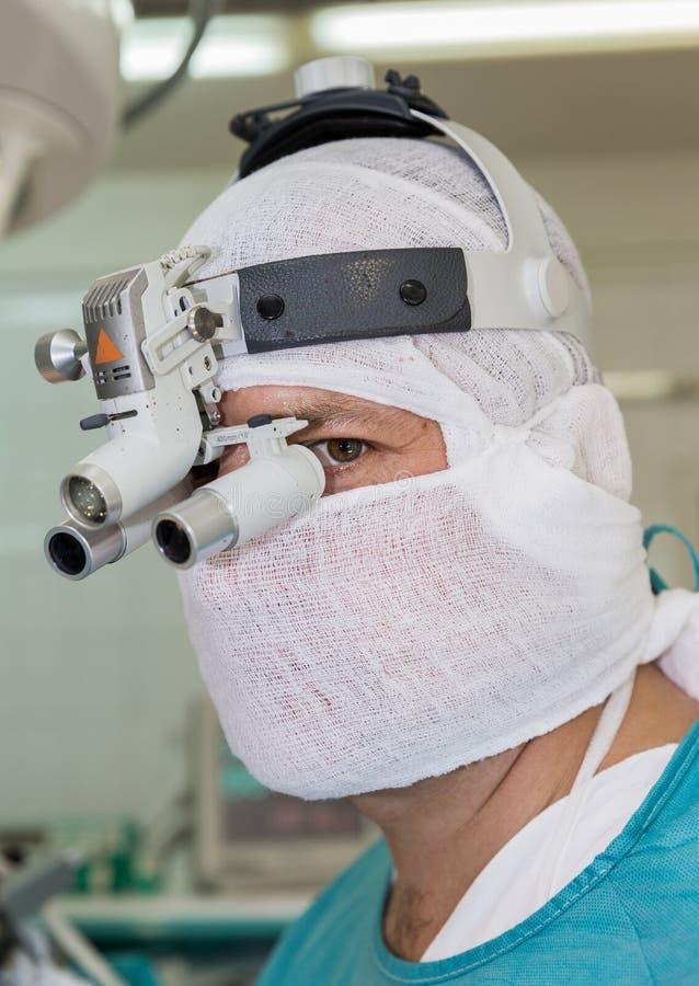 Chirurg met binoculaire hoofdband stock afbeelding