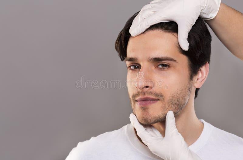 Chirurg plastyczny egzamininuje męską cierpliwą twarz, opróżnia przestrzeń obraz stock