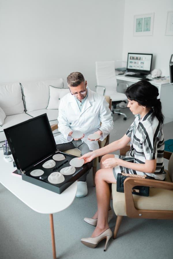 Chirurg plastyczny pokazuje kobiecie różnych rozmiary wszczepy fotografia stock