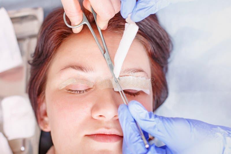 Chirurg trifft einen Verband auf die weiblichen Augenlider des Patienten nachher zu stockfotografie