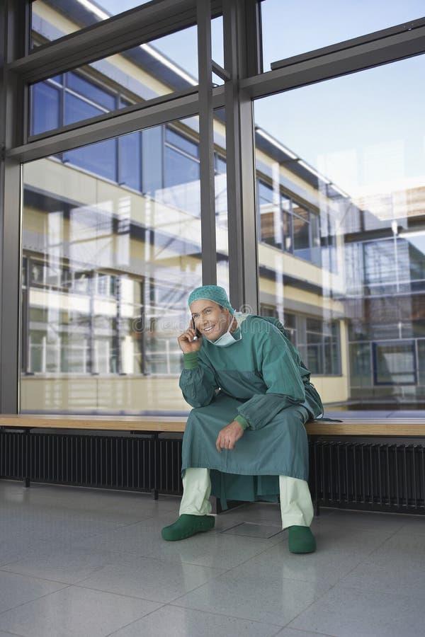 Chirurg-Using Cellphones In-Krankenhaus-Korridor stockfotos