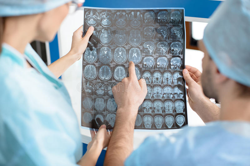 Chirurgen in den medizinischen Uniformen Röntgenstrahlbild überprüfend stockbild