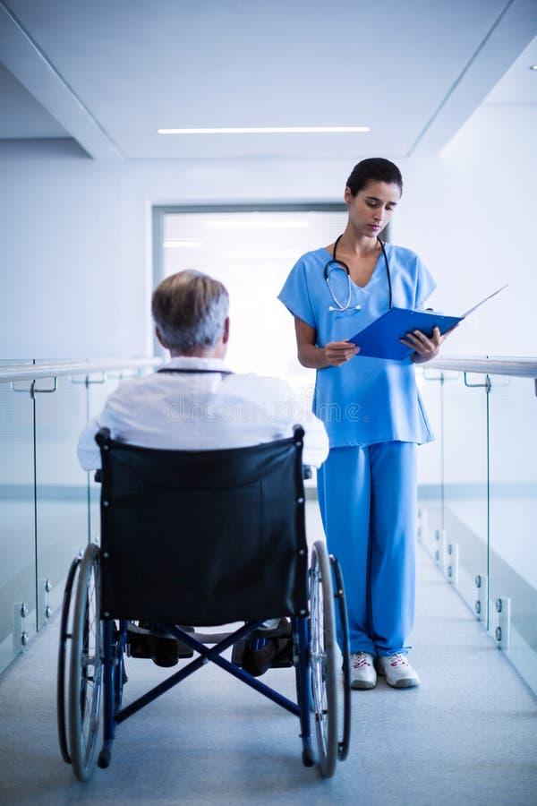 Chirurgen, die über ärztlichen Attesten sich besprechen stockbilder