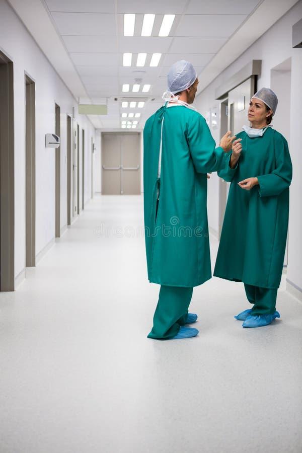 Chirurgen, die auf einander im Korridor einwirken lizenzfreie stockfotografie