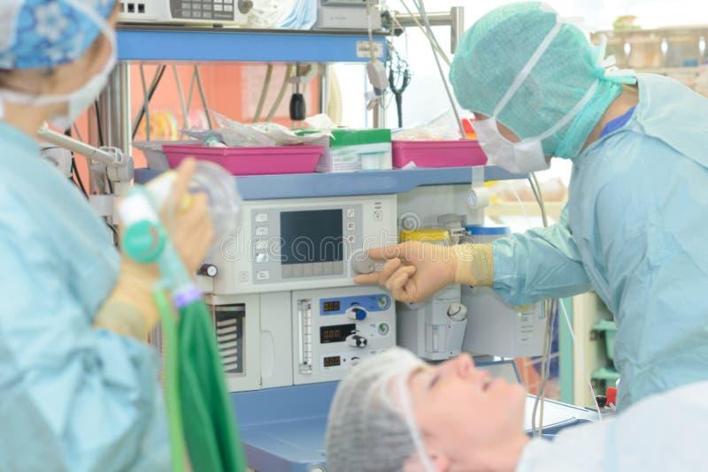 Chirurgen die met controlerende patiënt in chirurgische werkende ruimte werken royalty-vrije stock foto