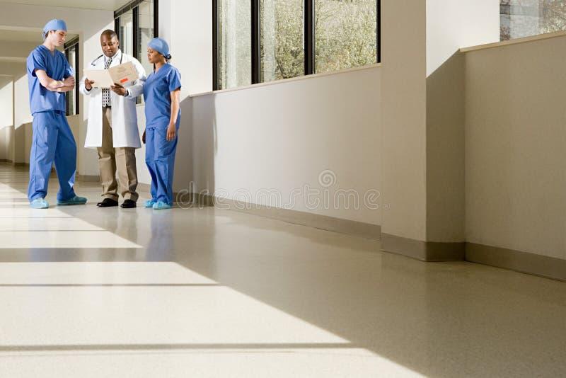 Chirurgen en arts die dossier bekijken stock foto
