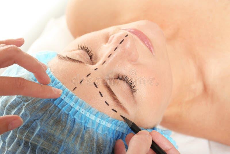 Chirurgenhanden die tekens trekken op vrouwelijk gezicht voor verrichting stock afbeeldingen