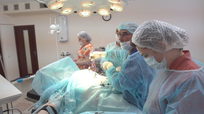 Chirurgenteam die met Toezicht op patiënt in chirurgische werkende ruimte werken Verrichting die laparoscopic materiaal met behul royalty-vrije stock foto's
