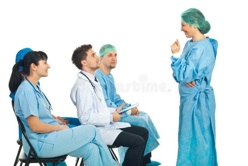 Chirurgfrau, die Diskussion mit Doktoren hat lizenzfreie stockfotografie
