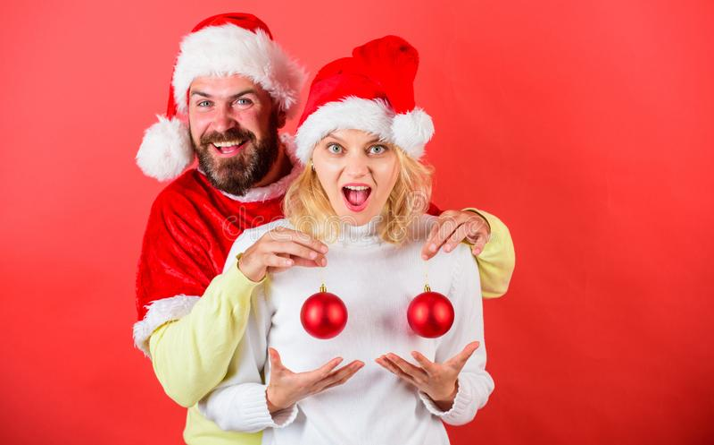 Chirurgia plastica Ornamento di natale delle palle della tenuta del cappello di Santa dell'uomo davanti ai seni femminili Impiant fotografie stock libere da diritti